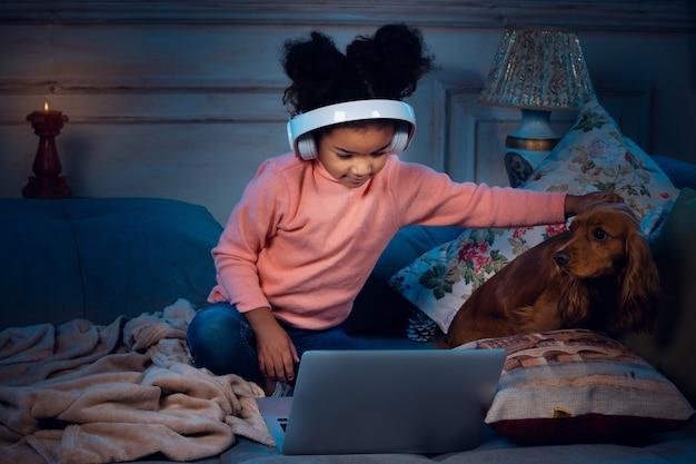ラップトップと家庭用デバイスを使用したビデオ通話中の幸せなアフリカ系アメリカ人の少女は、喜んで幸せそうに見えます。大晦日の前にサンタと話し、彼女の家族は漫画を見ています。