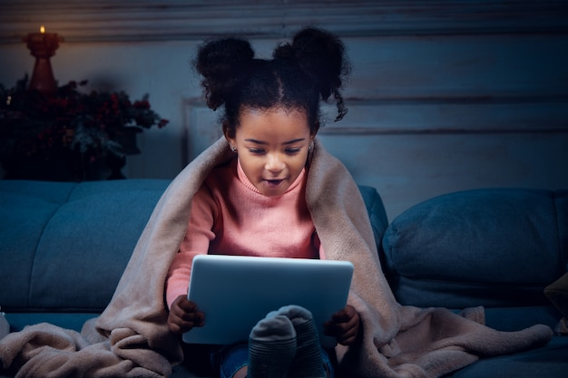 Happy african-american little girl during video call with laptop and home devices, looks delighted