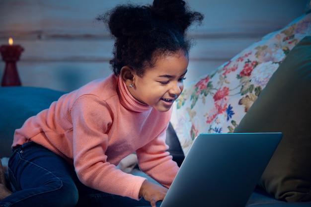 Felice bambina afroamericana durante la videochiamata con laptop e dispositivi domestici