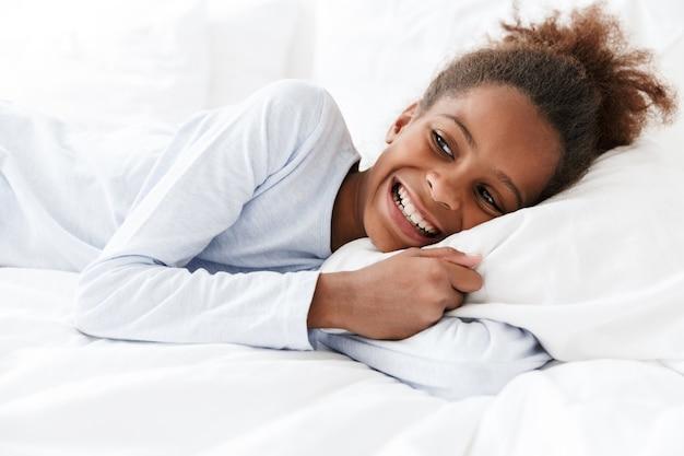 Счастливая афроамериканская маленькая девочка улыбается и лежит в постели у себя дома