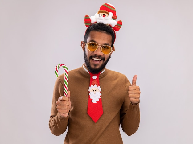Felice afroamericano uomo in maglione marrone e santa orlo sulla testa con divertente cravatta rossa che tiene il bastoncino di zucchero guardando la telecamera sorridendo allegramente mostrando i pollici in su in piedi su sfondo bianco