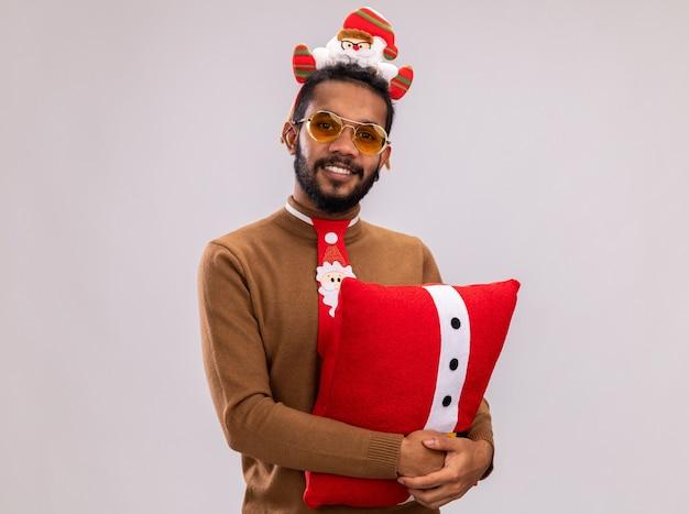 Uomo afroamericano felice in maglione marrone e orlo di santa sulla testa con cravatta rossa divertente che tiene il cuscino di natale che guarda l'obbiettivo con il sorriso sul viso in piedi su sfondo bianco