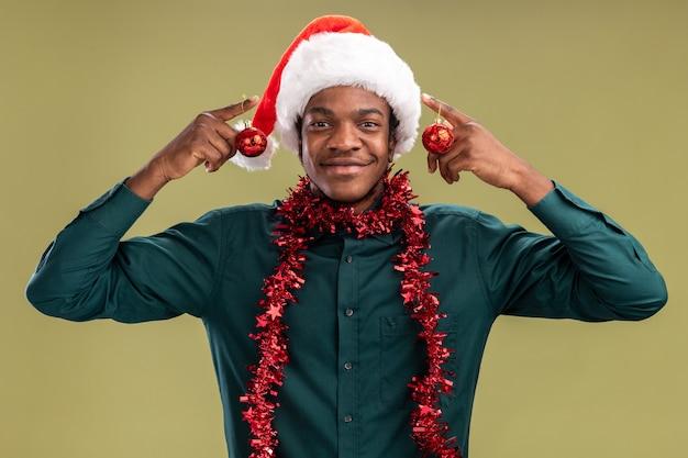 Счастливый афро-американский мужчина в шляпе санта-клауса с гирляндой держит елочные шары, улыбаясь, стоя над зеленой стеной