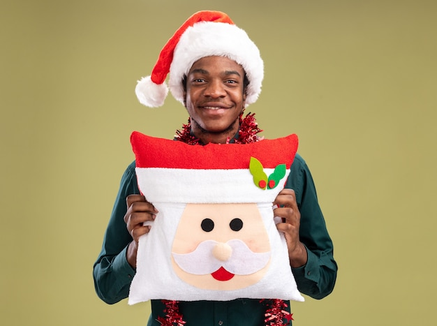 녹색 배경 위에 서있는 얼굴에 미소로 카메라를보고 크리스마스 베개를 들고 갈 랜드와 산타 모자에 행복 한 아프리카 계 미국인 남자