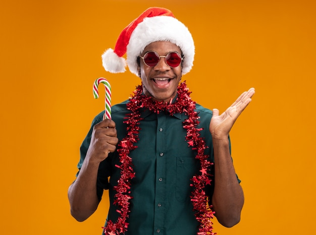 오렌지 벽 위에 올려 진 팔 서 유쾌 하 게 웃 고 사탕 지팡이 들고 안경을 쓰고 갈 랜드와 산타 모자에 행복 한 아프리카 계 미국인 남자