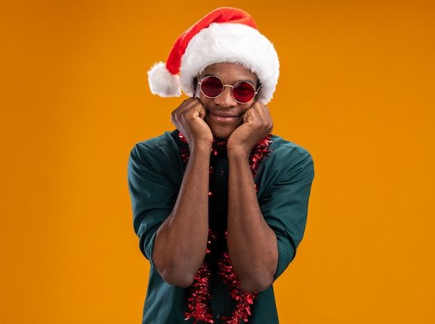 오렌지 배경 위에 유쾌하게 서있는 카메라를보고 안경을 쓰고 갈 랜드와 산타 모자에 행복 한 아프리카 계 미국인 남자