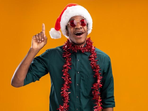 오렌지 벽 위에 서있는 새로운 아이디어를 갖는 검지 손가락을 보여주는 안경을 쓰고 갈 랜드와 산타 모자에 행복 한 아프리카 계 미국인 남자
