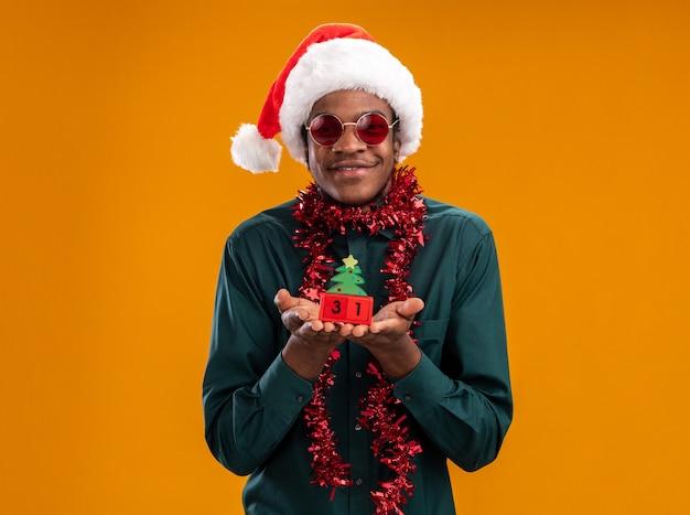 オレンジ色の背景の上に元気に立って笑顔のカメラを見て新年の日付とおもちゃの立方体を保持しているサングラスを身に着けている花輪とサンタの帽子で幸せなアフリカ系アメリカ人の男