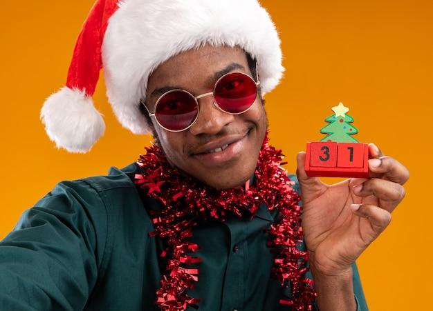 오렌지 벽 위에 서 웃 고 새 해 날짜 장난감 큐브를 들고 선글라스를 착용하는 갈 랜드와 산타 모자에 행복 한 아프리카 계 미국인 남자