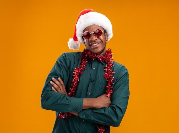 팔을 얼굴에 미소로 카메라를보고 선글라스를 착용하는 갈 랜드와 산타 모자에 행복 한 아프리카 계 미국인 남자는 오렌지 배경 위에 서 넘어