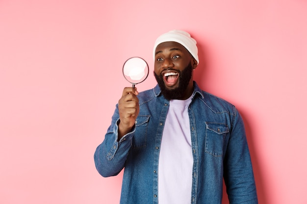 Happy african-american man looking through magnifying glass, smiling amazed, standing against pink background. copy space