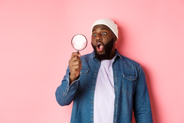 Happy african-american man looking through magnifying glass, smiling amazed, standing against pink background.