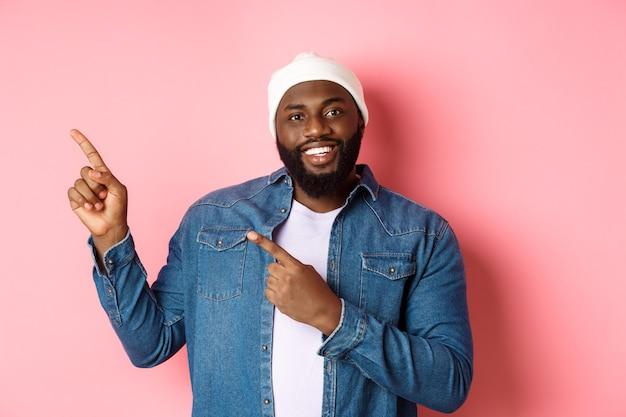 Felice uomo afroamericano che punta le dita nell'angolo in alto a sinistra, mostra il logo dell'offerta promozionale, sorride soddisfatto, indossa un berretto con giacca di jeans, sfondo rosa