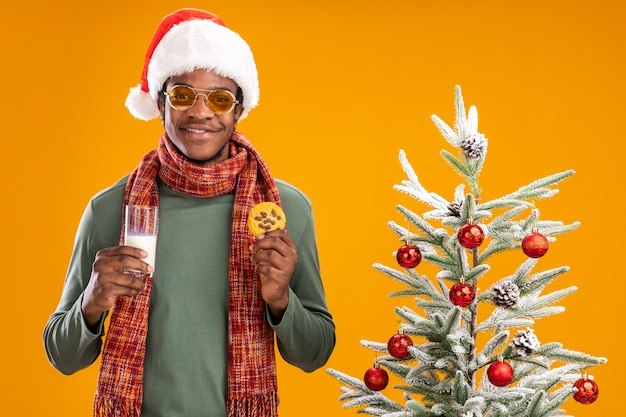 Felice uomo afroamericano in santa cappello e sciarpa intorno al collo tenendo un bicchiere di latte e biscotto sorridente in piedi accanto a un albero di natale su sfondo arancione