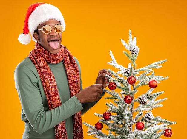 Felice afroamericano uomo in santa cappello e sciarpa intorno al collo guardando la telecamera spuntavano lingua in piedi accanto a un albero di natale su sfondo arancione