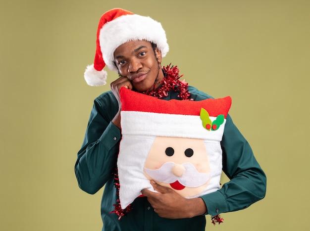 Uomo afroamericano felice in cappello della santa con la ghirlanda che tiene il cuscino di natale che guarda l'obbiettivo con il sorriso sul viso in piedi su sfondo verde