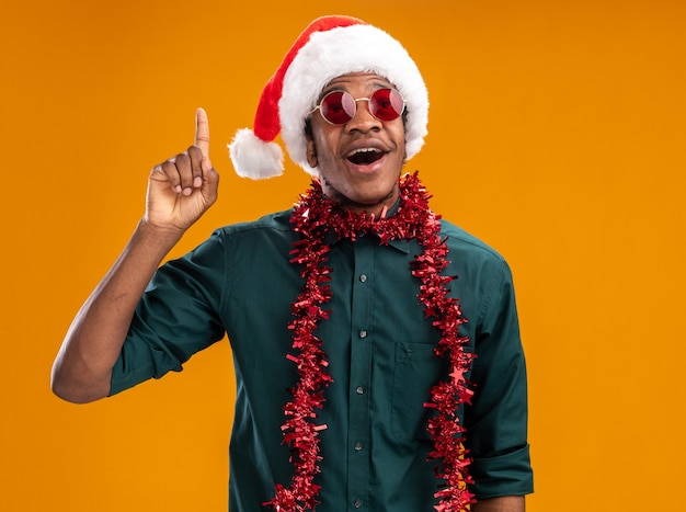 Happy african american man in santa hat with garland wearing glasses  showing index finger having new idea standing over orange wall