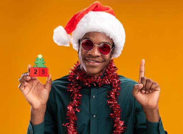 Uomo afroamericano felice in cappello della santa con la ghirlanda che indossa gli occhiali da sole che tengono i cubi del giocattolo con la data venticinque sorridente che mostra il dito indice che sta sopra la parete arancione
