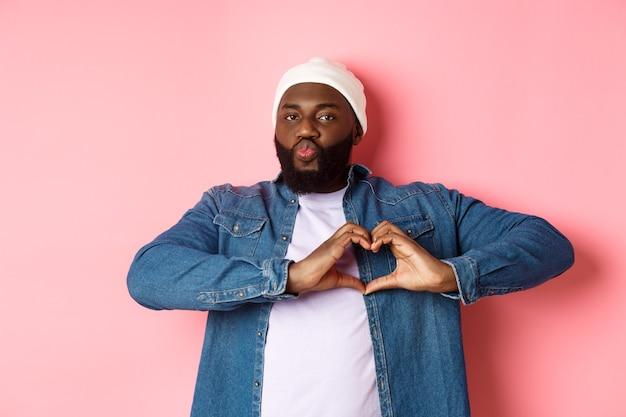 Felice uomo afroamericano che mostra il segno del cuore, ti amo gesto, labbra increspate per un bacio mentre si sta in piedi su sfondo rosa