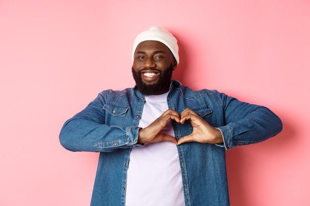 Felice uomo afroamericano che mostra il segno del cuore, ti amo gesto, sorride alla macchina fotografica, sfondo rosa