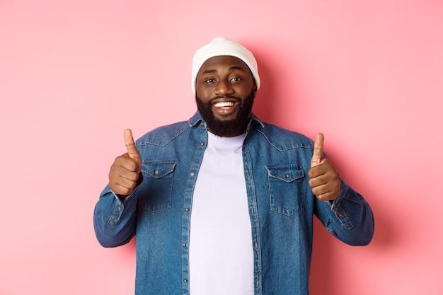 ピンクの背景の上に立って、何か良いもののように、大いに賞賛し、承認で親指を立てて示す幸せなアフリカ系アメリカ人の男