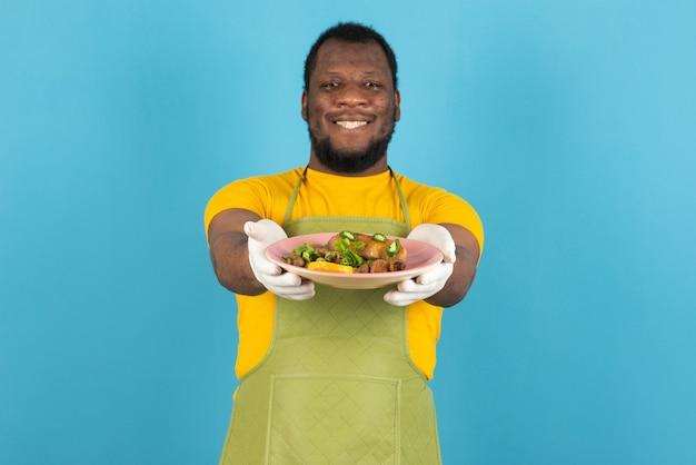 Felice uomo afroamericano con la barba, che indossa un grembiule con un piatto di cibo in mano, si erge sul muro blu.