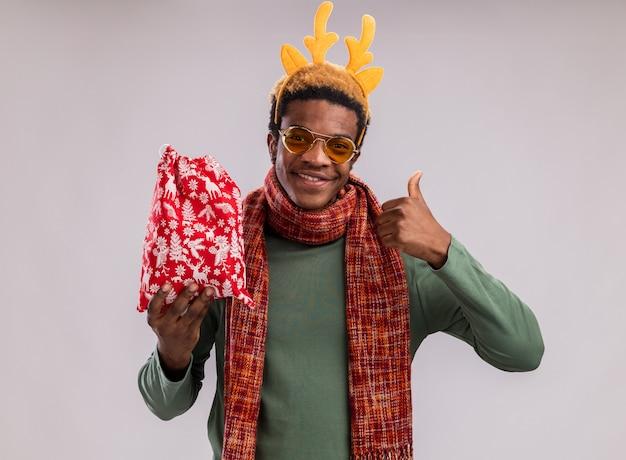 녹색 배경 위에 서있는 엄지 손가락을 보여주는 미소를 카메라를보고 선물과 함께 빨간 산타 가방을 들고 목 주위에 사슴 뿔과 스카프와 함께 재미있는 테두리와 함께 행복 한 아프리카 계 미국인 남자
