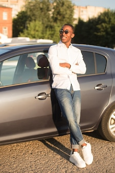 夏の車の横にある幸せなアフリカ系アメリカ人