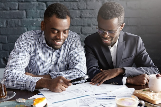 Happy african american office workers dressed in formal clothing having cheerful looks, studying and amalyzing legal documents on table using magnifying glass while getting papers ready for meeting