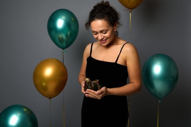 행복한 아프리카계 미국인 예쁜 여자는 황금 리본으로 장식된 반짝이는 반짝이 포장지에 선물을 보고 공기 풍선과 함께 회색 벽 배경 위에 포즈를 취하는 것을 기뻐합니다. 크리스마스, 생일 개념