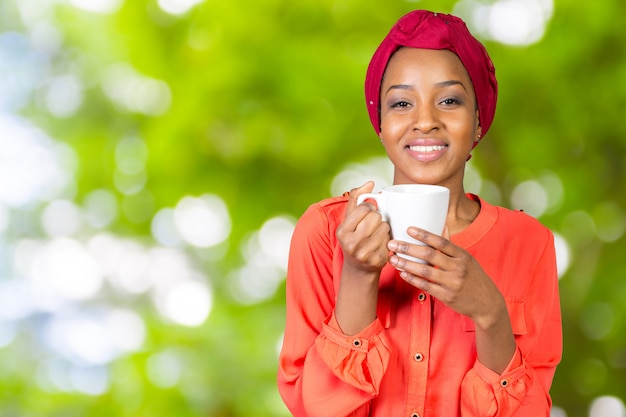 Happy african american woman drinking tea  cup or mug
