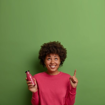 Счастливая афроамериканка пьет свежий фруктовый смузи, держит напиток из супер-продуктов в стеклянной бутылке, указывает указательным пальцем на зеленую стену, будучи в хорошем настроении. здоровый образ жизни