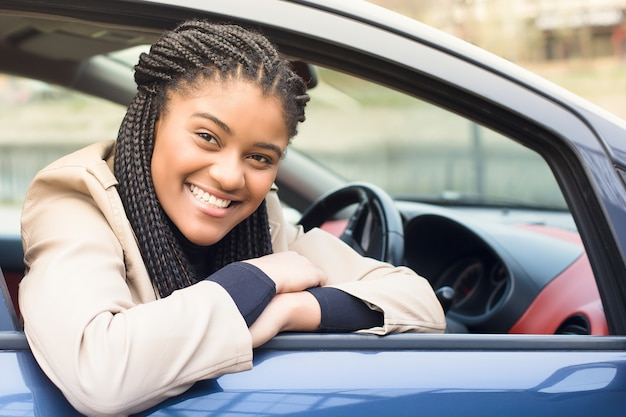 車の運転、秋冬の幸せなアフリカ系アメリカ人の女性。