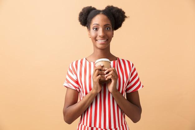 テイクアウトコーヒーと紙コップを保持しているカジュアルな服装で幸せなアフリカ系アメリカ人女性、