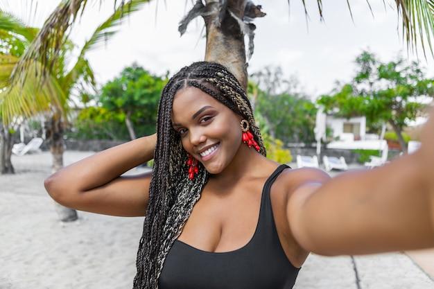 셀카를 찍고 여름 옷에 행복 한 아프리카계 미국인 여자. 웃 고 카메라를 보고 해변에 쾌활 한 여자.