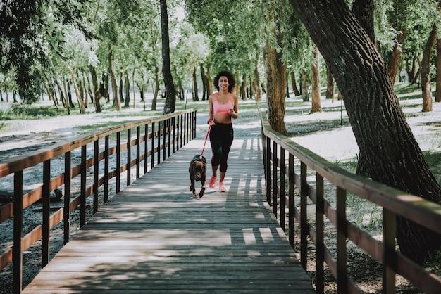 Happy african american woman jogging on footbridge