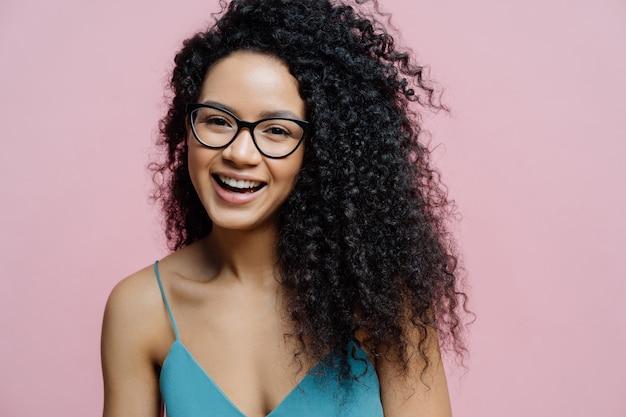 Счастливая афроамериканская женщина смеется от радости, имеет здоровую темную кожу, вьющиеся волосы, изолированные на пастельном розовом фоне