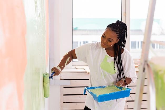 그녀의 새 아파트에서 행복 한 아프리카 계 미국인 여자 그림 벽. 리노베이션, 재 장식 및 수리