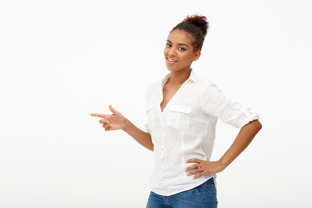 左を指す幸せなアフリカ系アメリカ人女性