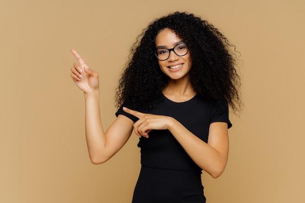 Счастливая афроамериканка показывает вверх и в сторону, демонстрирует пустую копию места для вашей рекламы