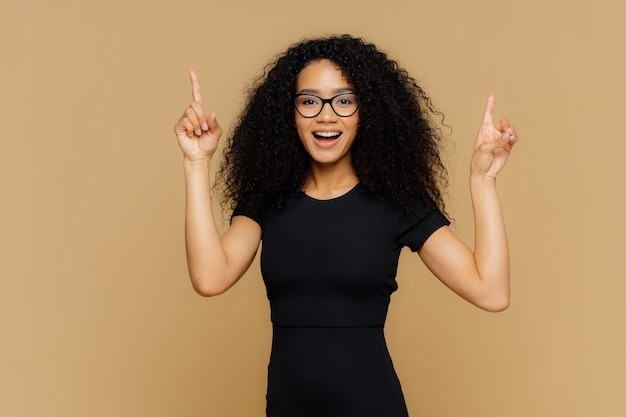 Happy african american woman points above with both index fingers