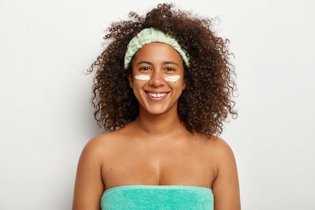 행복한 아프리카 계 미국인 여자는 얼굴 크림을 눈 아래에두고 건조한 피부를 가지고 있으며 회춘 치료를 즐기고 수건에 싸서 부드러운 머리띠를 착용하고 긍정적으로 미소 짓습니다.
