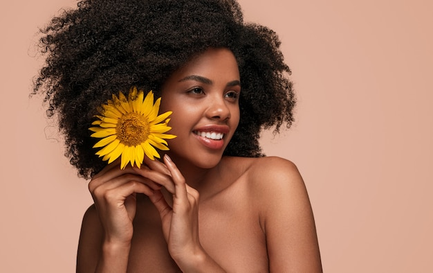 Happy african american woman putting flower in hair