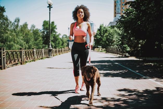Happy african american woman in sportswear jogging.