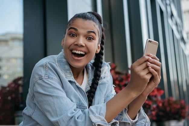 Счастливый афро-американских женщина с помощью мобильного телефона, глядя в камеру