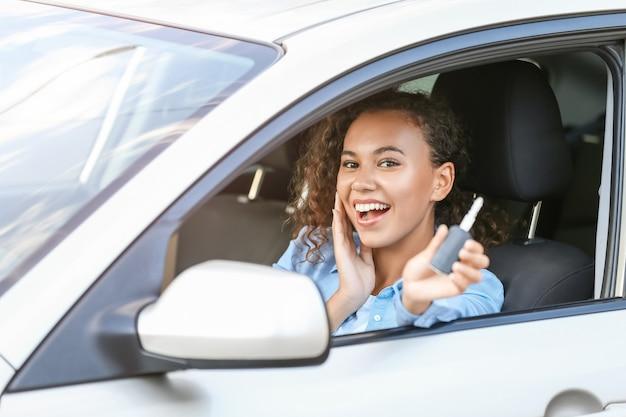 新しい車に鍵が座っている幸せなアフリカ系アメリカ人女性