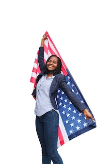 Happy african american woman wrapped and holding with outstretched arms the u.s. flag on a white background.