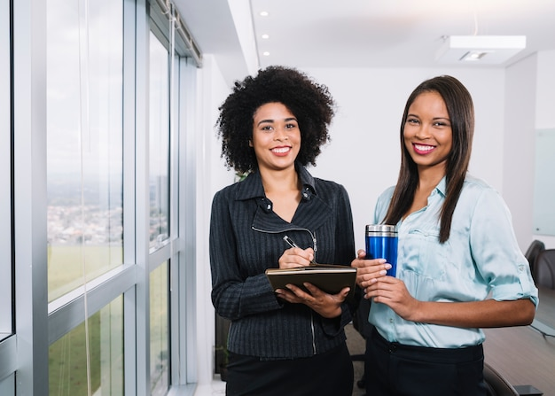 Happy african american women with documents and thermos near window in office
