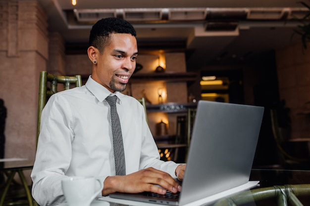 Счастливый афро-американский молодой бизнесмен, используя ноутбук