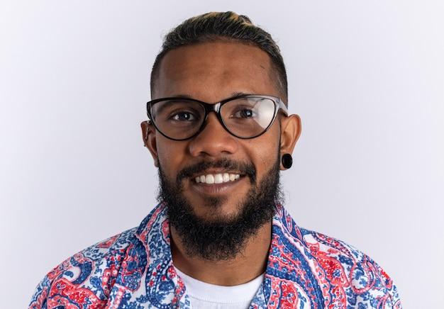Felice giovane afroamericano in maglietta colorata con gli occhiali guardando la telecamera sorridendo allegramente